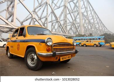 KOLAKATA, INDIA -JAN 12 : Yellow Ambassador taxi of Kolkata wait for travellers in the background of Howrah bridge on January 12, 2018 in Kolkata, West Bengal,India.