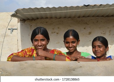 Kolayat, Bikaner, Rajasthan /India,April  11,2018: Three young girls in Rajasthani dress in style standing by theInside the boundary wall of a house made of clay in a village of Kolayat