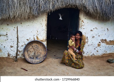 Kolayat, Bikaner, Rajasthan /India,April  11,2018:  Beautiful young girl wearing a Rajasthani dress with her baby at  sitting the door of a mud hut made in a village in Kolayat