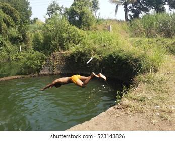 KOLHAPUR  INDIA - NOV 06 2016-rural boy jumping in water well for swimmimg fun at kolhapur,india