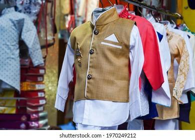 KOLKA, INDIA - Apr 21, 2021: multi color dress csherwani kurta hanging from hangar in a garment shop for sale