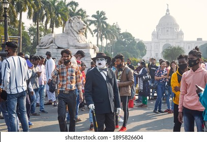 Kolkata, 01-01-2021: A performer, Charlie Chaplin lookalike with his iconic hat and moustache, entertaining crowd of visitors near Victoria Memorial and requesting to mandatorily wear face mask.