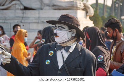Kolkata, 01-01-2021: Portrait of a performer, Charlie Chaplin lookalike with his iconic hat and moustache, standing among celebrating crowd of visitors near Victoria Memorial on new year's day.