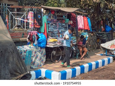 Kolkata, 01-09-2021: Two street vendor in their garment stall on a wheeled cart, stranded on footpath. Several readymade garments are seen on retail display.