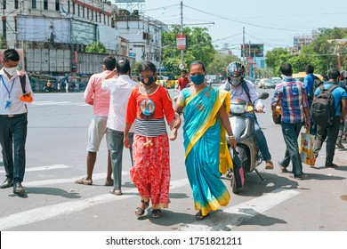 Kolkata, 06/02/2020: India Unlock 1.0. People standing at a bus stop, waiting for bus / public transport. A mother and her daughter wearing face mask are seen waiting there among crowds.