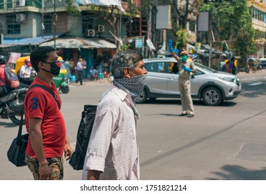 Kolkata, 06/02/2020: Two office going people wearing face mask are seen walking in street. A traffic surgeon is standing there in middle of the road, controlling traffic in background.
