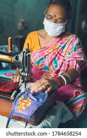 Kolkata, 07/23/2020: A simple looking Indian woman stitching handmade cloth face masks inside her home. A vintage looking sewing machine and some unfinished masks are seen.