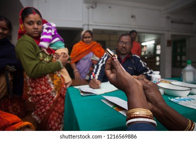 Kolkata, 24 Parganas (S), India - 12th January 2013: Mother with their Children have come for checkup in the clinic or the hospital and to take immunisation. The nurse is preparing doses of injection.