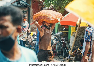 Kolkata, 7/26/2020: A sweating market vendor carrying a large sack of potatoes on head, seen walking through middle of market, in harsh sunlight. Other buyers are seen around him, wearing face mask.