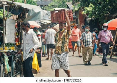 Kolkata, 7/26/2020: A sweating market vendor carrying a large vegetable basket on head, seen walking through middle of market, in harsh sunlight. Other buyers are seen around him, wearing face mask.