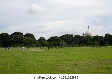 Kolkata, Bengal / India - August 08 2015: Boys playing cricket on the Maidan in kolkata. In the background the Victoria Memorial.