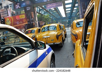 KOLKATA (CALCUTTA), WEST BENGAL, INDIA - OCTOBER 02, 2014: A white taxi among yellow ones. Ambassador, modeled after the British Morris Oxford, was the first car to be made in this country.
