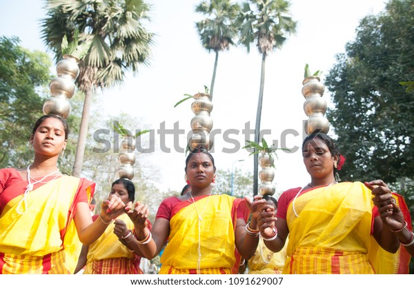 KOLKATA - DECEMBER 28: Bengal tribal woman dancing with pots on their head during a Bengali Heritage Rally to kick off North American Bengali Conference 2015  in Kolkata, India on 28th December 2014.