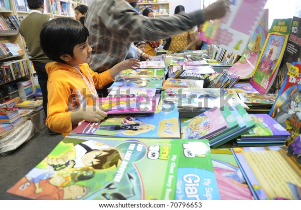 KOLKATA- FEBRUARY 4: A small kid is being helped by her grandfather to identify books amongst many, during the 2011 Kolkata Book Fair in Kolkata, India on February 4, 2011.