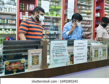 Kolkata, India, 03/31/2020: Medicine salespersons busy at medicine counter, all seen wearing protective face masks. Photo taken inside a homeopathic medicine shop, during lockdown in city.