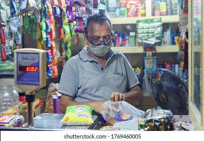 Kolkata, India, 07/04/2020: A middle aged shop owner, wearing face mask is working in his shop. During Unlock 3.0, in process of easing lockdown restrictions, more number of shops are opening.