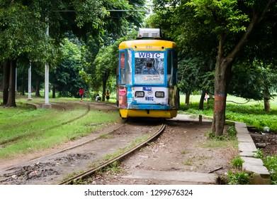"KOLKATA, INDIA - 15 January 2019: Historic and heritage tram of Calcutta running on the track in ""Maidan"" near park street area near a tramway depot at Esplanade, Kolkata on a sunny winter morning."
