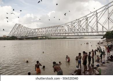 Kolkata / India 2016, 8 October,  Howrah Bridge( Rabindra Setu)  built in 1943, People bathing on malik ghat of hooghly river at Howrah bridge during morning, West Bengal India