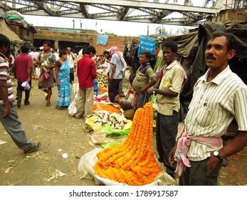 KOLKATA - INDIA - 29 MARCH 2013. Customers and traders of huge Mullik Ghat Flower Market on old Indian street.