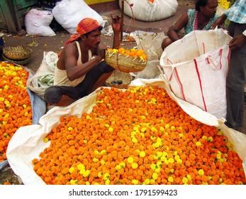 KOLKATA, INDIA -29 March 2013: Flower market in Kolkata city, people selling different flowers and flower garlands near Howrah Bridge in Kolkata, West Bengal, India