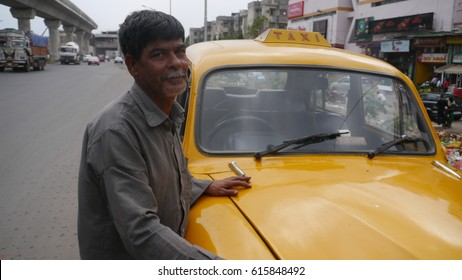 KOLKATA, INDIA - 7 MARCH, 2017: An unidentified Indian man standing near yellow taxi at street and looking at camera.