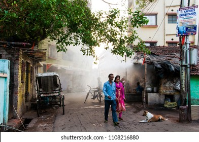 KOLKATA, INDIA - APRIL 06, 2018: a couple walking on the street of kolkata with the smoke flying on the back in the morning