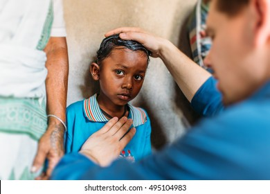 KOLKATA, INDIA   APRIL 15, 2015: Poor indian boy in blue t-shirt looks in the camera with big eyes while missionary prays for him