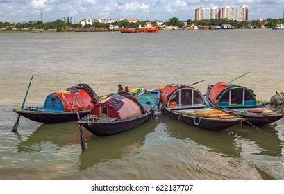 KOLKATA, INDIA, APRIL 16, 2017: Wooden boats lined up at the Ganges river bank at Princep ghat Kolkata with the city skyline as the backdrop. These boats are used for boating rides on the river.