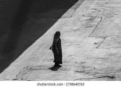 Kolkata, India - April 2020: Lockdown for COVID-19 - Lady crossing the road