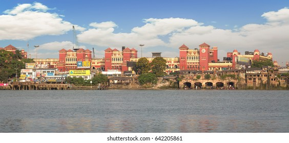 KOLKATA, INDIA, APRIL 28, 2017: Cityscape and Howrah Station as viewed from Mallick Ghat on the other side of river Hooghly. Howrah railway station is a historic colonial structure on the river bank.