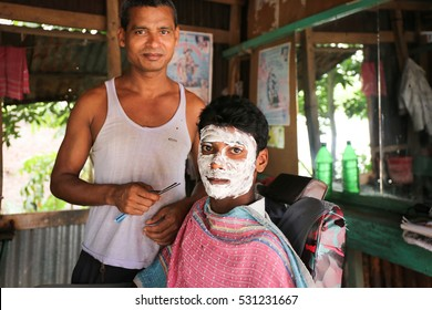 KOLKATA, INDIA - APRIL 30, 2016: In a local barber shop in India a young man's handsome face is fully foamed and creamed in, and will get his face shaved soon.