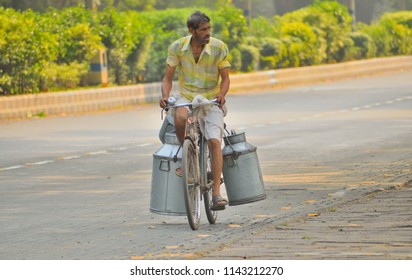 Kolkata, India - April 30, 2017: A milkman cycling down the road.