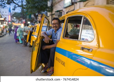 Kolkata, India - April 5, 2017: Portrait of an indian taxi driver with his antique oldtimer yellow taxi on the streets of Kolkata