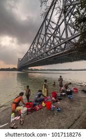Kolkata, India - April 6, 2017: View of the Howrah bridge with people taking a bath in Hooghly river in Kolkata, West Bengal, India.