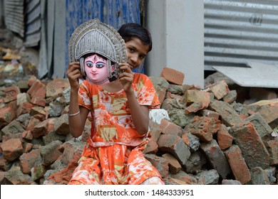 Kolkata, India - August 13 2019:  A child playing in the street with a mask of Goddess Durga makes every day a special children day.