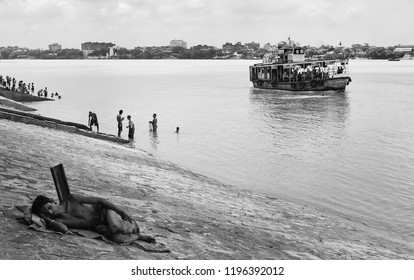 KOLKATA, INDIA - AUGUST 19, 2011: View across the Hooghly river (Ganges) with public ferry, people bathing and asleep on August 19, 2016, Kolkata, India.