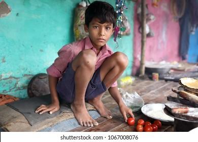 KOLKATA - INDIA - DECEMBER 11, 2017: Unidentified street child prepares food in a slum on December 11, 2017 in Kolkata, India