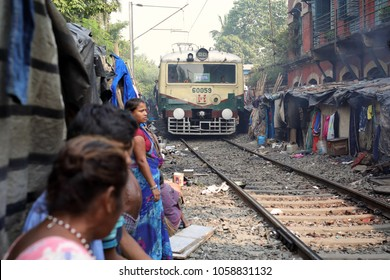 KOLKATA - INDIA - DECEMBER 12, 2017: Unidentified people watch the train in a slum on December 12, 2017 in Kolkata, India