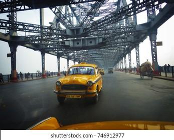 Kolkata, India - December 15, 2013: Yellow Ambassador taxi cab crossing Howrah bridge in Kolkata city, West Bengal, India