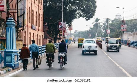 KOLKATA, INDIA - DECEMBER 25, 2015: People walking, riding bicycle and cars running on the street in Kolkata, India