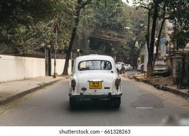 KOLKATA, INDIA - DECEMBER 25, 2015: White classic car run on the street with trees in Kolkata, India