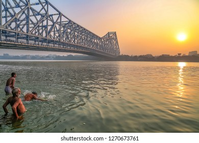 Kolkata, India, December 26,2018: Historic Howrah bridge Kolkata at sunrise with view of the Ganges river ghat with people. Howrah bridge is a famous cantilever bridge and the busiest in India