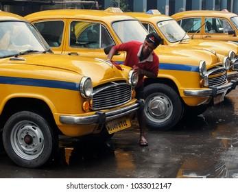 Kolkata, India - December, 8th, 2017. Taxi driver washing his car. Early morning on the street of Kolkata, India.