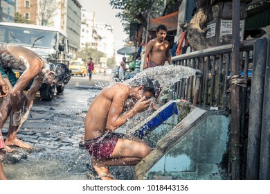 KOLKATA, INDIA - FEBRUARY 04, 2018: A young boy is taking a public outdoor shower in the Streets of Kolkata