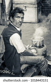 KOLKATA, INDIA - FEBRUARY 04, 2018: Black and white portrait of an old man cooking at a make shift street side kitchen