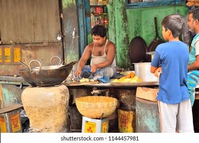 Kolkata, India - February 19, 2017: People buying snacks from a roadside eatery.