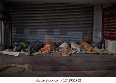 Kolkata, India, February 2016. A group of people sleep in the street at night at the entrance to a shop.