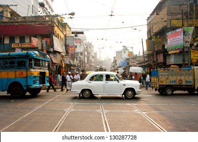 KOLKATA, INDIA - JAN 13: Antique white Ambassador car down the busy street on January 13, 2013 in Kolkata, India. First Ambassador was produced by the Yellow Cab Manufacturing Company in 1921