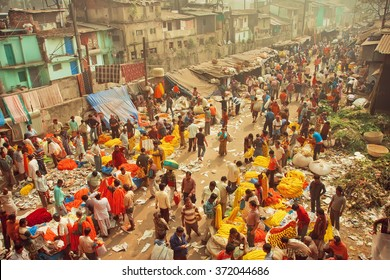 KOLKATA, INDIA - JAN 13: Customers and traders of huge Mullik Ghat Flower Market on old indian street on January 13, 2016. More than 125 years old market has near 2000 sellers workers every day
