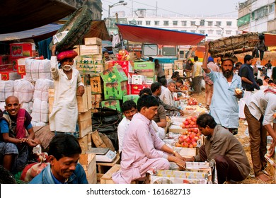 KOLKATA, INDIA - JAN 13: Fruits traders sell apples and oranges on the street market on January 13, 2012 in Calcutta. Only 0.81% of the Kolkata's workforce employed in the primary sector (agriculture)